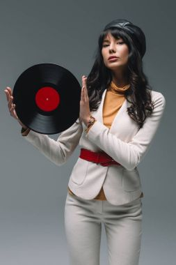 attractive brunette woman in white suit holding vinyl isolated on gray
