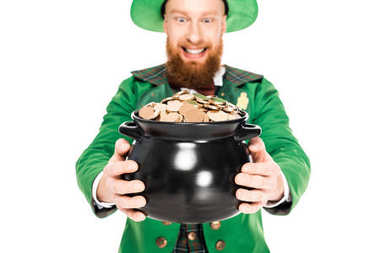 excited leprechaun in green suit looking at pot of gold, isolated on white