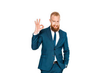 handsome bearded businessman standing with hand in pocket and showing ok sign isolated on white