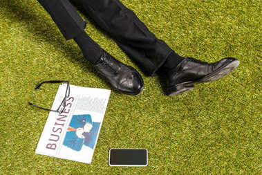 low section of businessman in stylish leather shoes, eyeglasses, newspaper and smartphone with blank screen on green grass