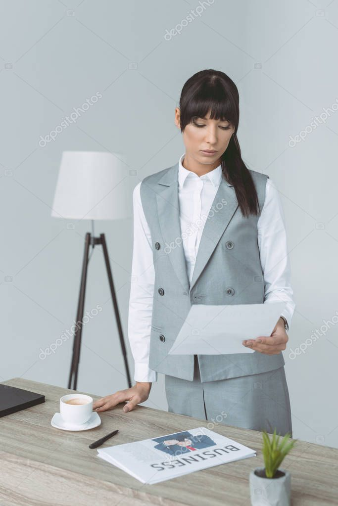 businesswoman looking at document isolated on gray