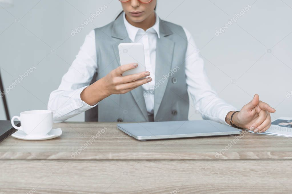 cropped image of businesswoman looking at smartphone isolated on gray