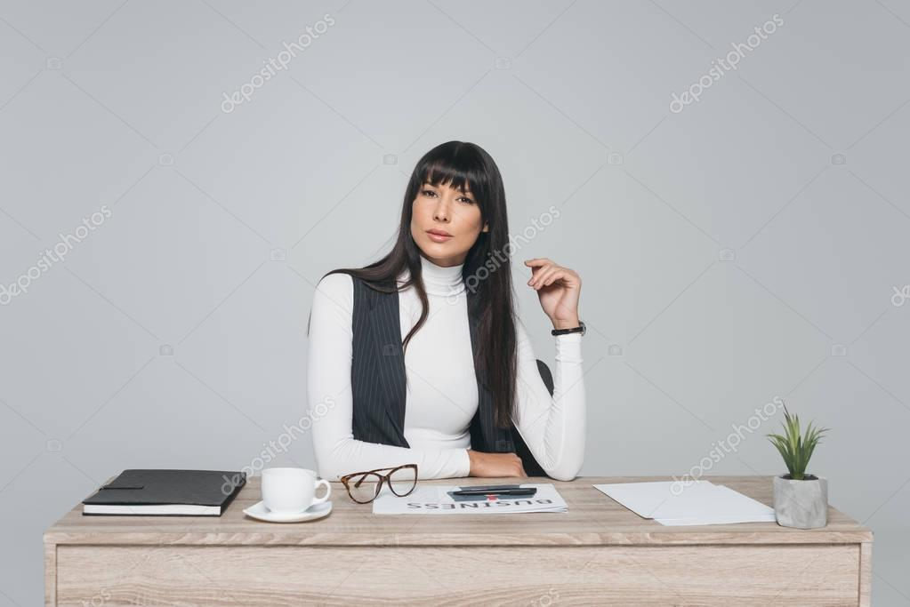 attractive brunette businesswoman sitting at working table isolated on gray
