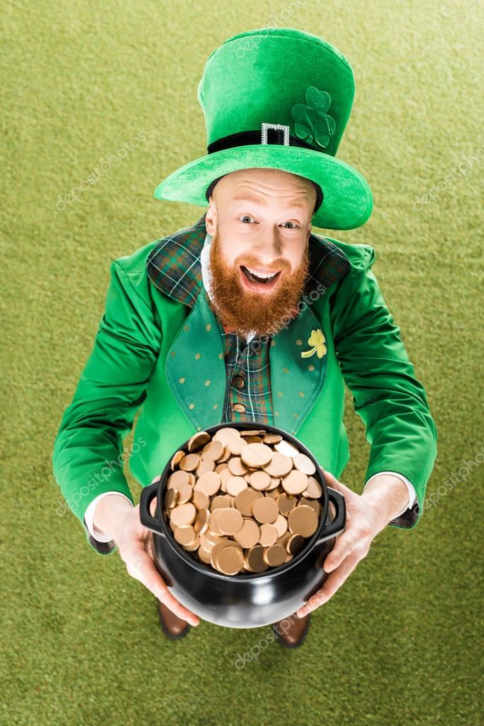 excited leprechaun holding pot of gold on green grass