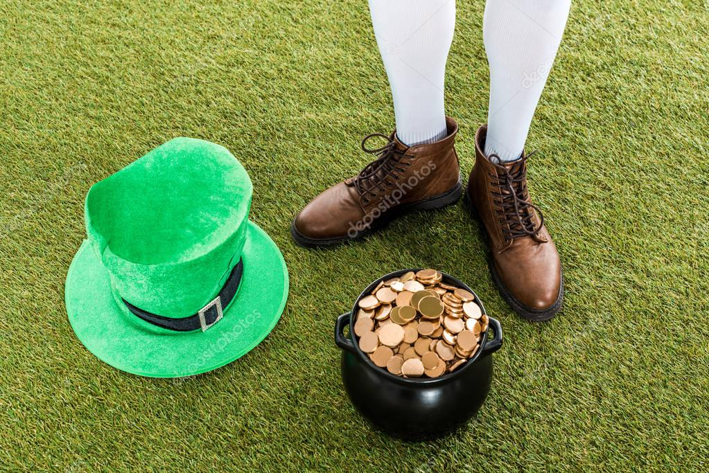 cropped view of leprechaun with pot of gold and hat on green grass