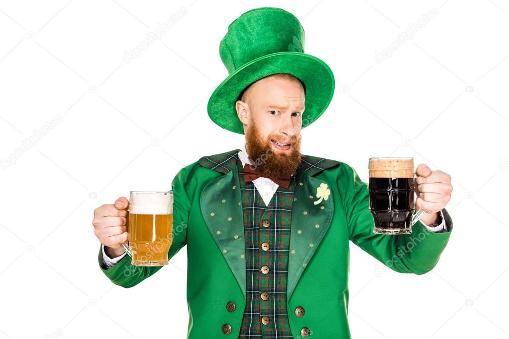 bearded man in green costume and hat holding glasses of beer and looking at camera isolated on white