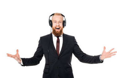 excited bearded young businessman listening music in headphones and looking at camera isolated on white
