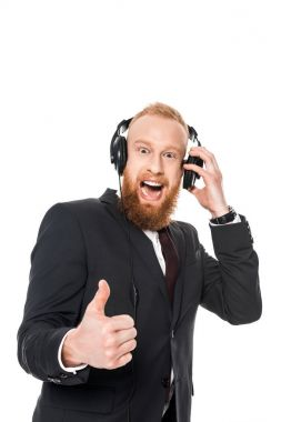 cheerful young businessman listening music in headphones and showing thumb up isolated on white