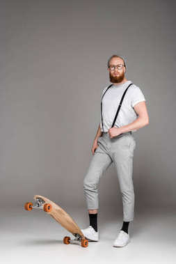 stylish bearded man in suspenders standing with skateboard and looking at camera on grey