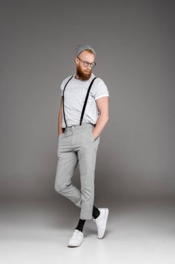 handsome bearded man in suspenders and spectacles standing with hands in pockets and looking down on grey