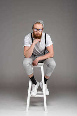 stylish bearded man in eyeglasees sitting on stool and looking at camera on grey
