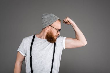 stylish bearded man in suspenders and hat looking at biceps isolated on grey