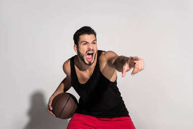 aggressive young sportsman holding basketball ball, pointing with finger and screaming on white