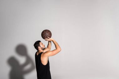 side view of athletic young sportsman playing basketball on white
