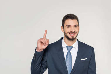 smiling young businessman pointing up with finger and looking at camera isolated on grey