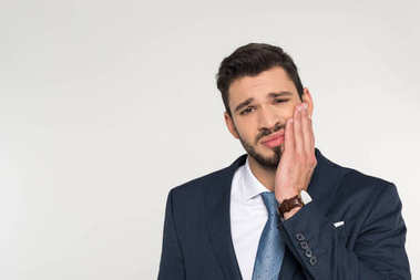 young businessman with toothache looking at camera isolated on grey