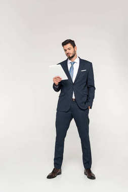 full length view of confident young businessman using digital tablet isolated on grey