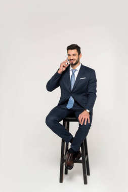 smiling young businessman talking on smartphone while sitting on stool and looking away isolated on grey