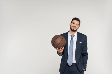 young businessman holding basketball ball and smiling at camera isolated on grey