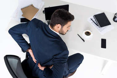 high angle view of young businessman having backache while sitting at workplace