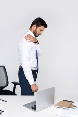 side view of young businessman suffering from pain in shoulder while standing at workplace