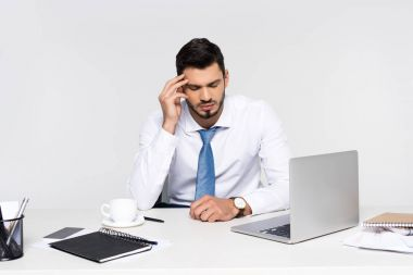 overworked young businessman suffering from headache while sitting at workplace