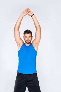 handsome sporty man stretching hands and looking at camera isolated on white