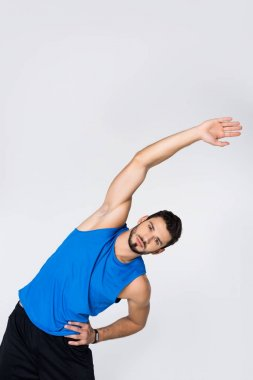 sportive young man doing side bend isolated on white