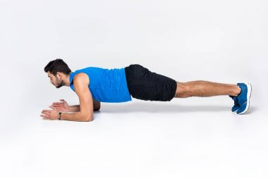 sportive young man doing plank on white