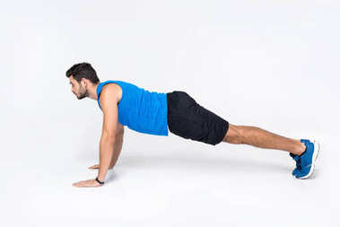 side view of young man doing push ups on white