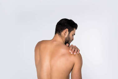 back view of young shirtless man with pain in shoulder isolated on white