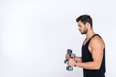 side view of athletic man working out with dumbbells isolated on white