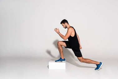 side view of athletic man doing step aerobics on block