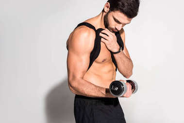 handsome young man working out with dumbbell