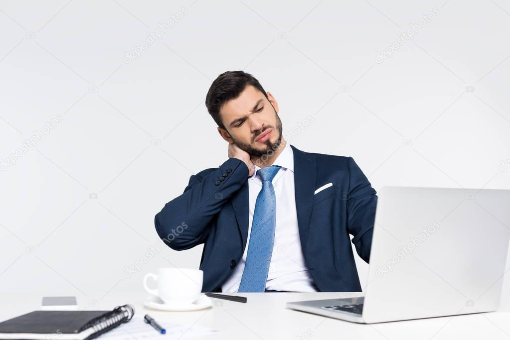 young businessman with closed eyes suffering from pain in neck while using laptop at workplace