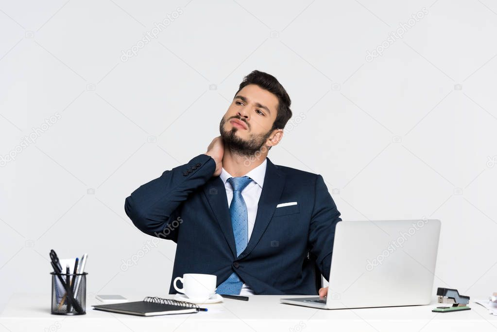 young businessman suffering from pain in neck while using laptop at workplace