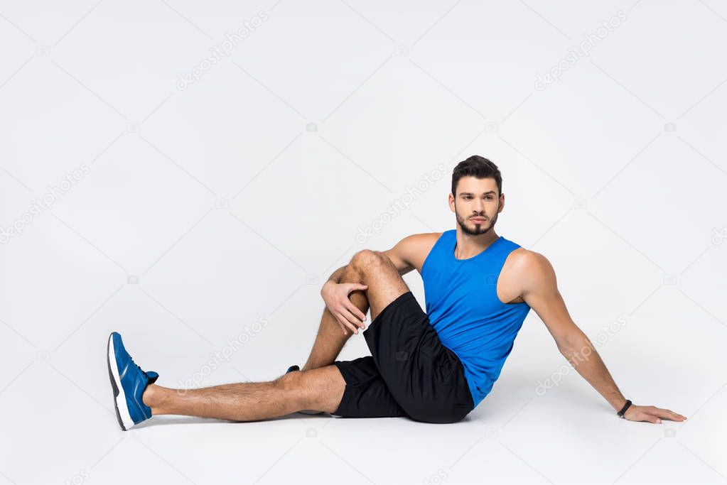 handsome young man stretching leg while sitting on white