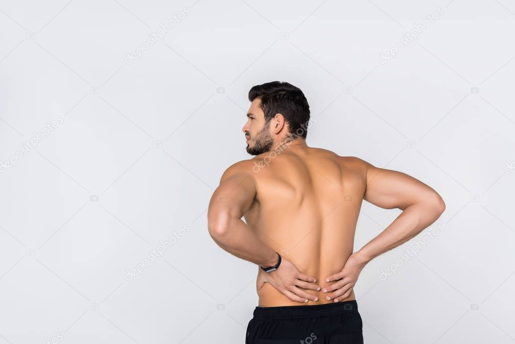 back view of young shirtless man with back pain isolated on white
