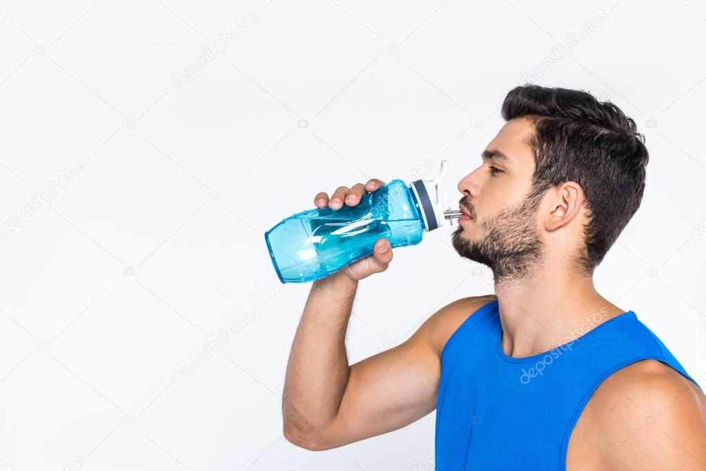 side view of sporty young man drinking water from fitness bottle isolated on white