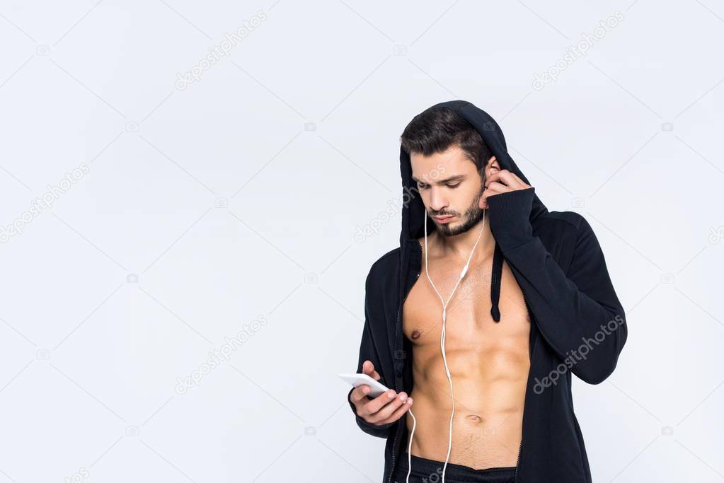 muscular young man in unzipped hoodie listening music with earphones isolated on white
