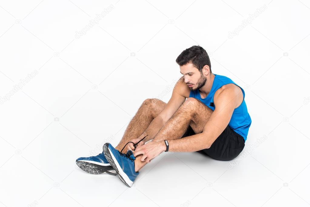 sportive young man lacing up sneakers before run on white