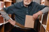 Fotografia immagine potata di bibliotecario di capelli grigi che tiene libro