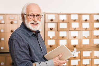 smiling senior male archivist holding book and looking at camera