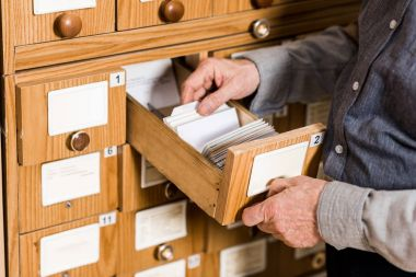 cropped image of senior male archivist searching for catalogs