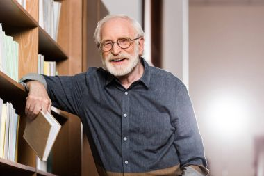 grey hair librarian holding book and leaning on shelf