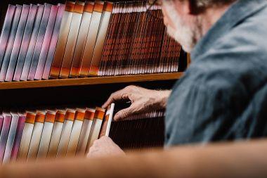 grey hair librarian taking book from shelf