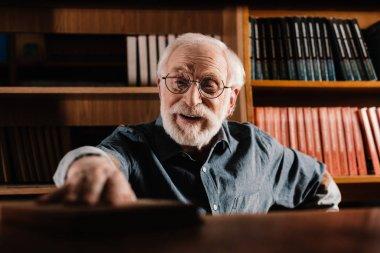 smiling grey hair librarian taking book from shelf