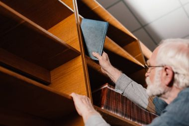 grey hair librarian taking book from shelf