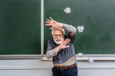 senior lecturer protecting himself of falling crumpled pieces of paper