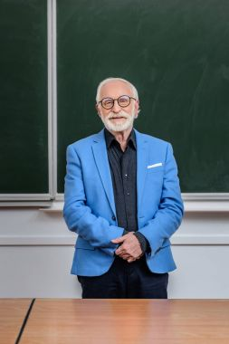 smiling senior lecturer standing in classroom and looking at camera